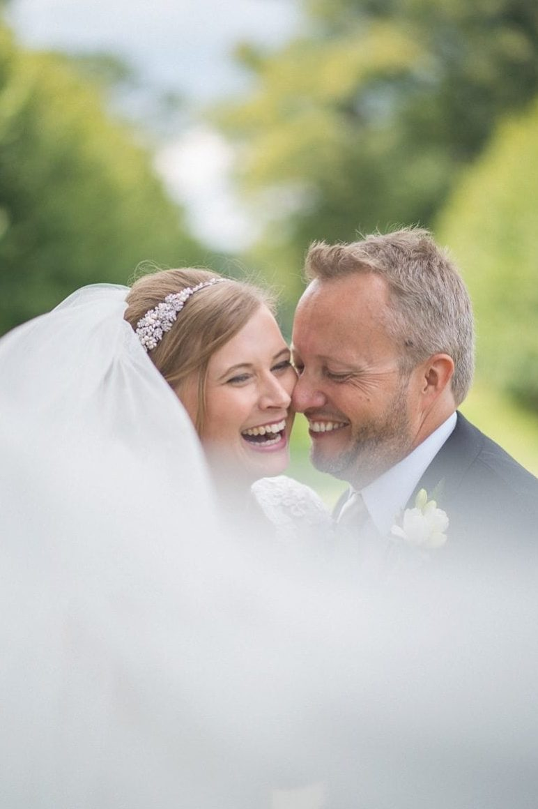 Bride and Groom laughing with each other at their Coworth Park Wedding