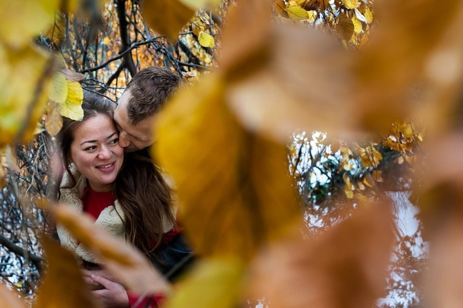 A couple hugging through autumn leaves on their Copenhagen pre-wedding shoot
