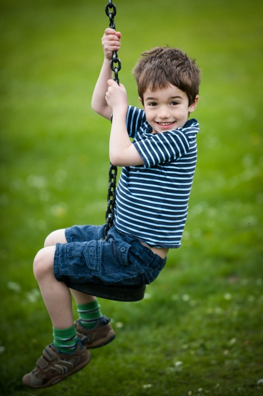 Boy sits smiling on a zip line at a Kemsing playground