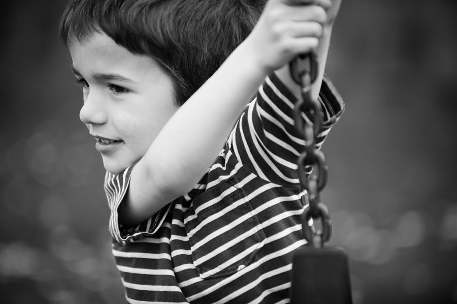 Boy looks to the left as he holds on to a chain