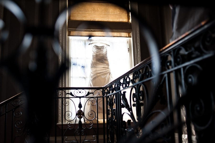 Wedding dress hanging in a window at Great Fosters gallery and staircase