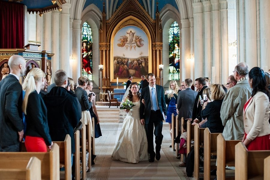 Bride and groom walking out of the church at Copenhagen winter destination wedding