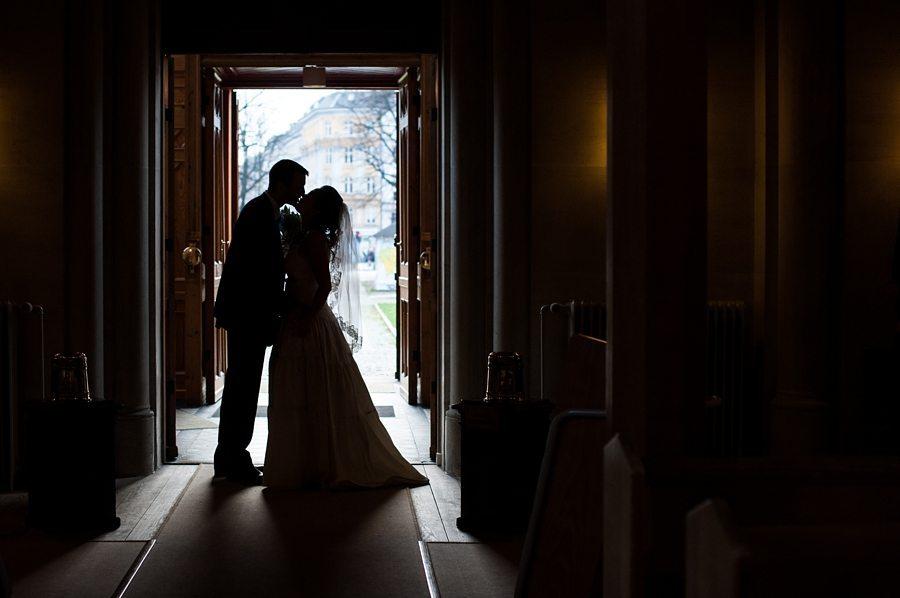 Copenhagen wedding photographer photo of bride and groom kissing in the church doorway
