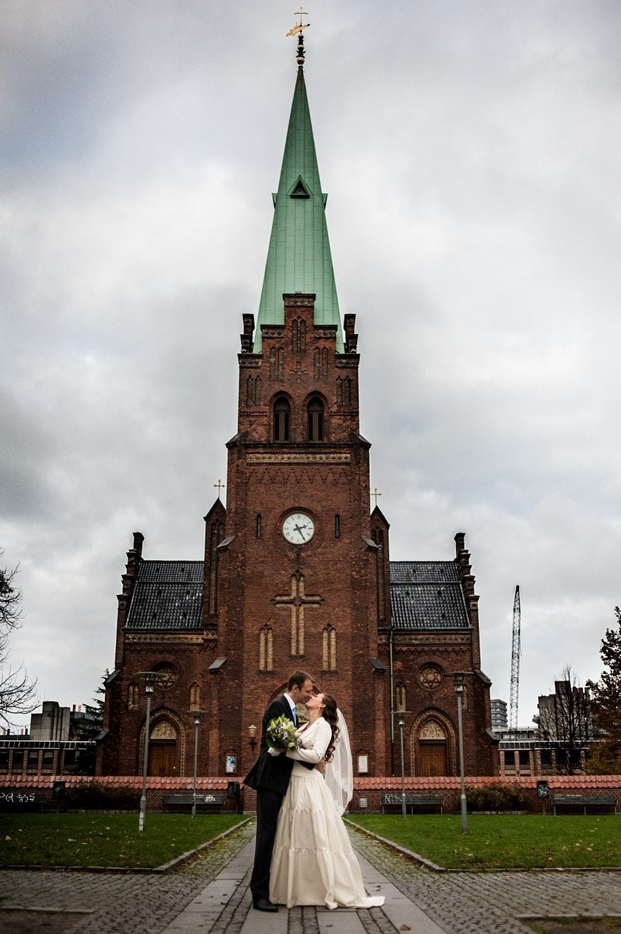 Copenhagen wedding photographer bride and groom kissing in front of their church in Nørrebro at their winter wedding