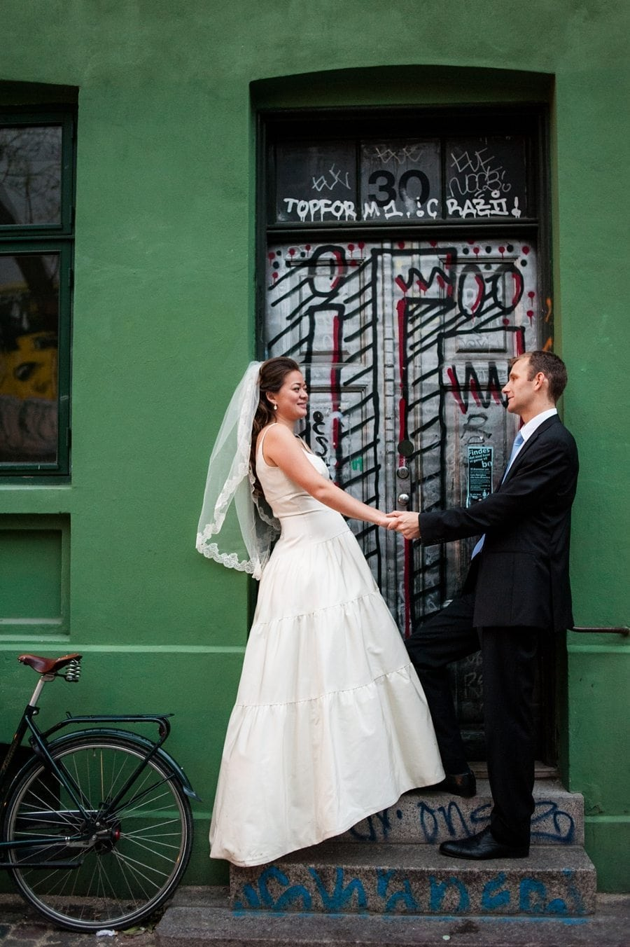 Bride and groom standing in a Copenhagen doorway at their destination winter wedding
