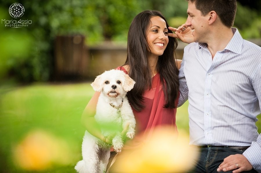 Couple smiling at each other holding their dog