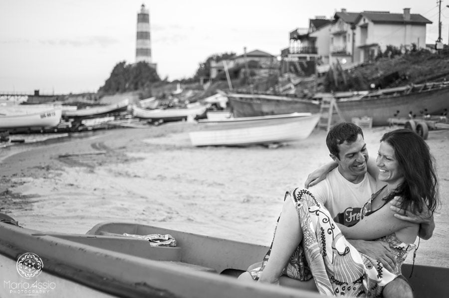 Couple sitting in a boat on the beach with a lighthouse, boats and fishing huts, destination wedding photographer Black Sea Evening pre wedding shoot