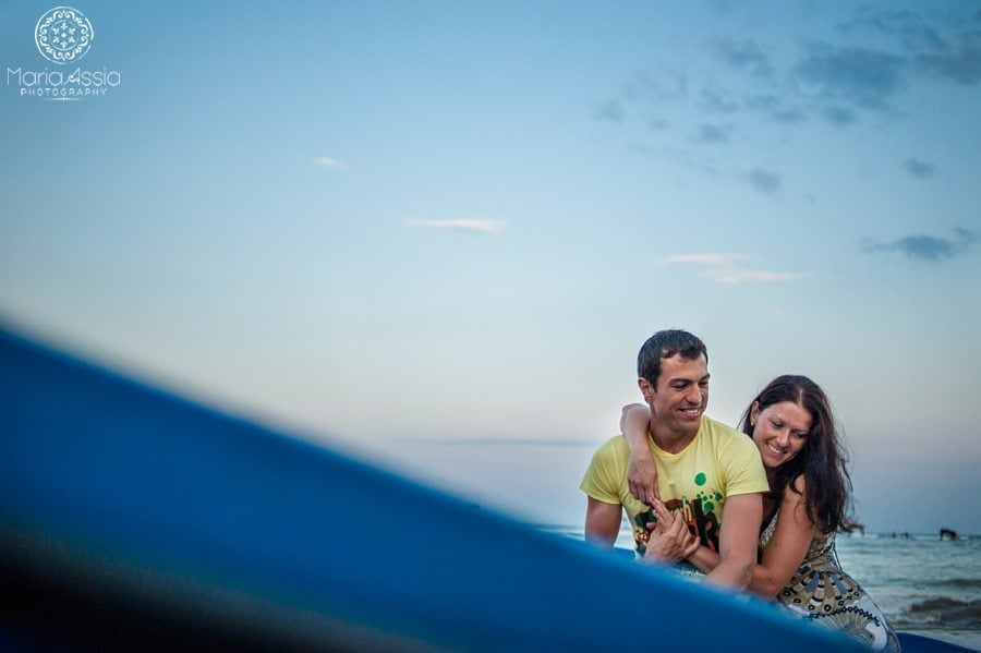 Evening pre wedding shoot at the Bulgarian Black sea couple sitting in a boat with the evening sky behind them