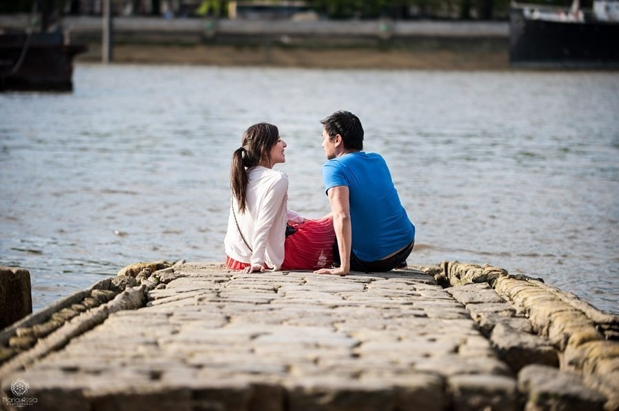 Engaged couple sitting on a London dock on their Southbank pre-wedding shoot by Maria Assia Photography