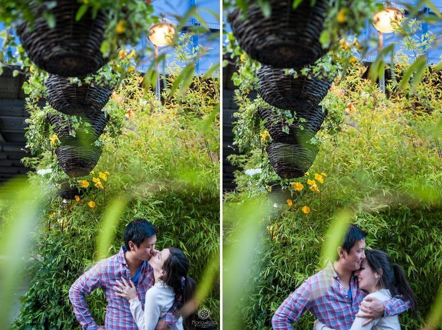 Couple kiss and hug surrounded by planters and greenery