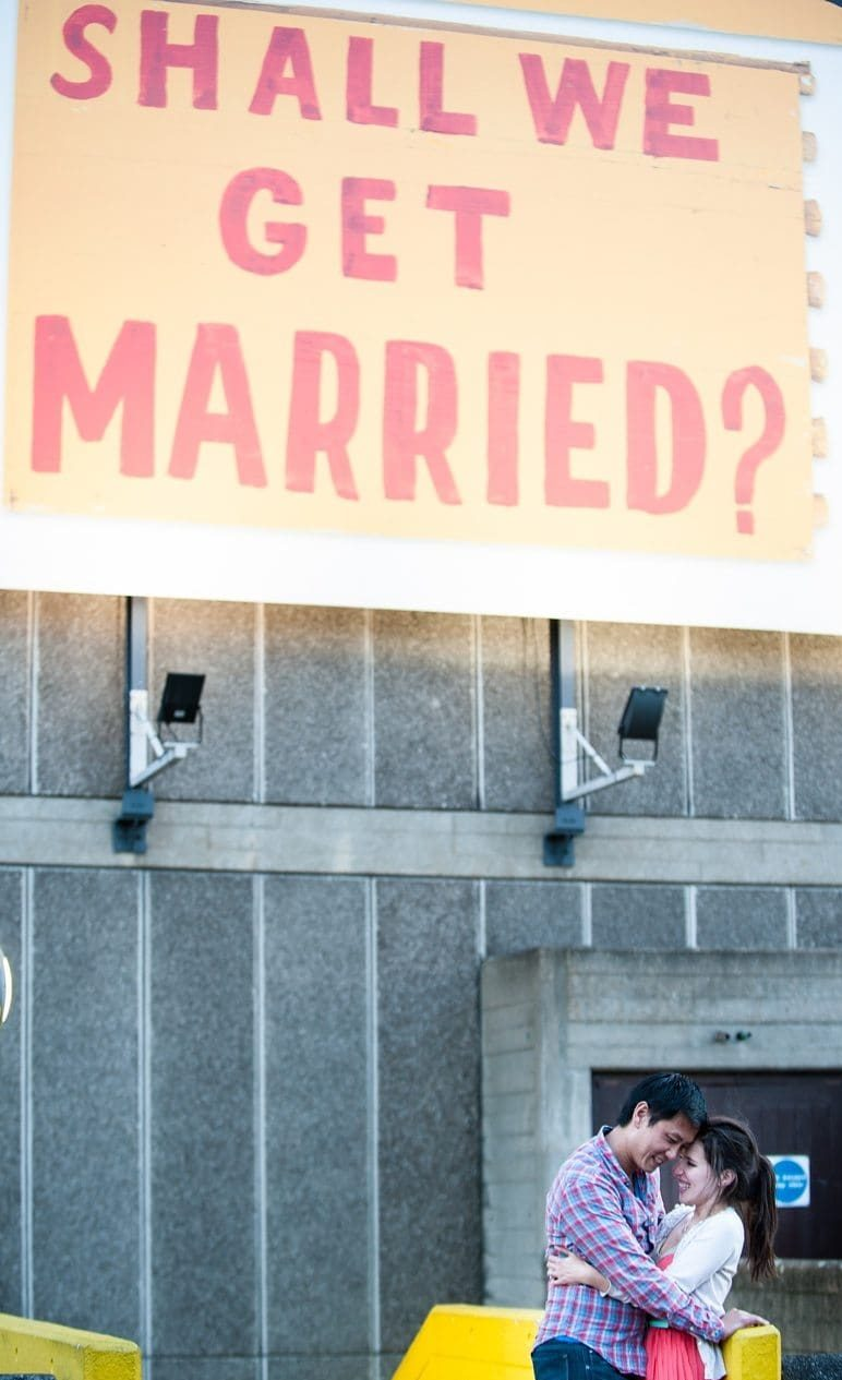 Engaged couple hug laughing under a Shall we get married billboard
