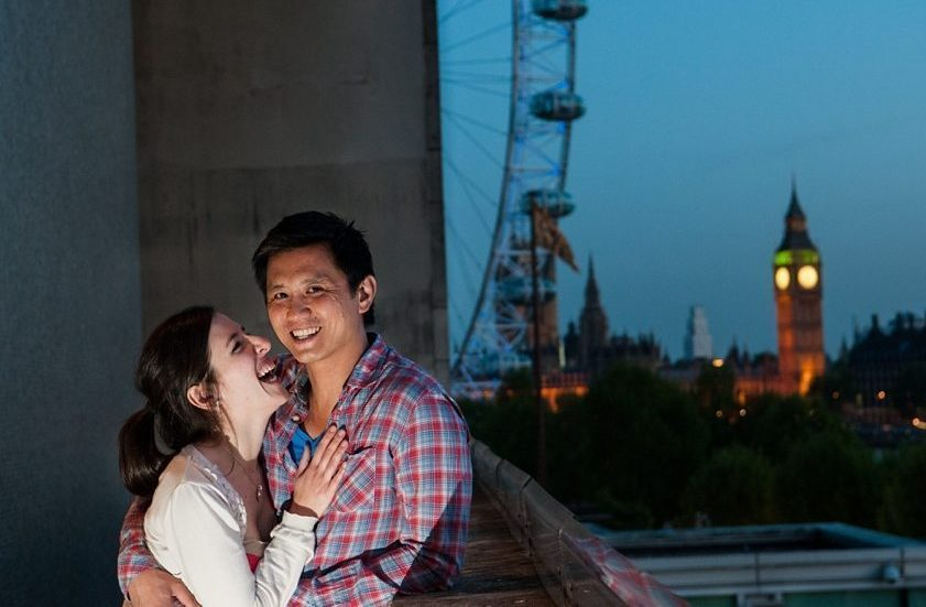 Pre-wedding couple laugh with Big Ben and the London Eye in the background