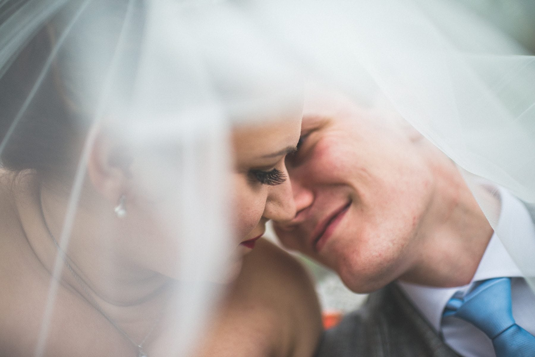 Creative real wedding photography or a bride and groom just about to kiss under the bride's veil