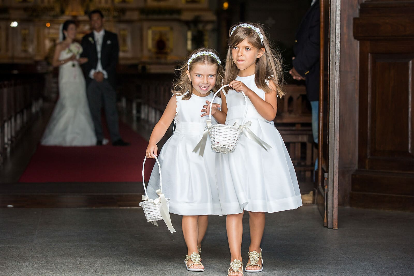 Flower girls walk out of the church ahead of the bride and groom