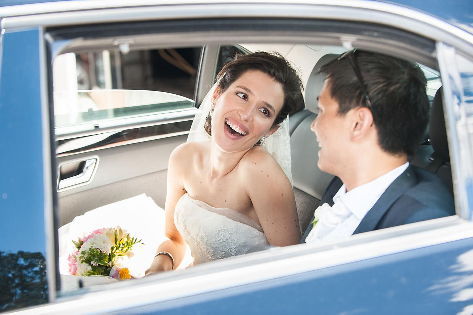 Bride and groom smile at each other in their porto destination wedding car