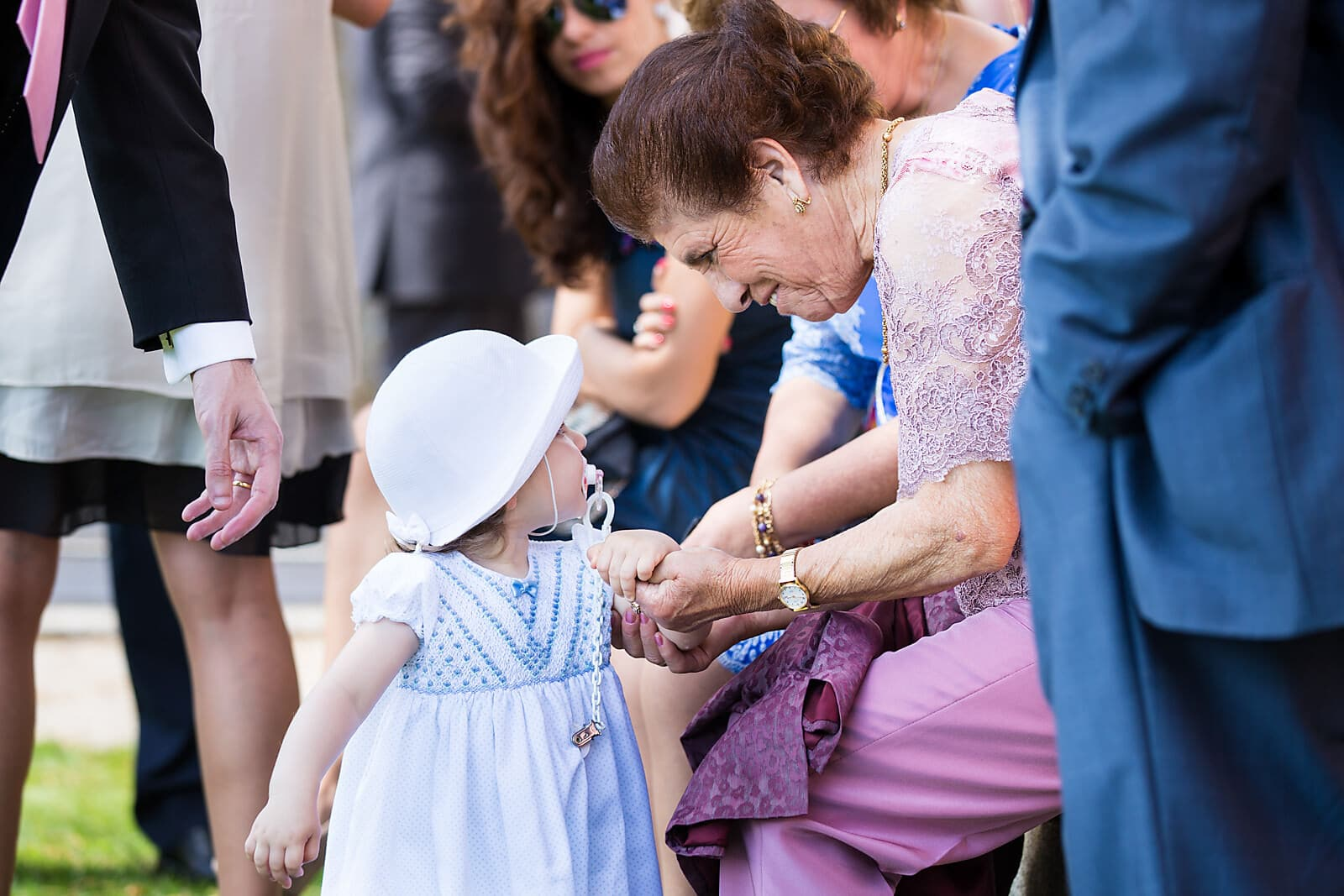 a great-grandmother holds her great-grandchilds hand at a wedding in Porto