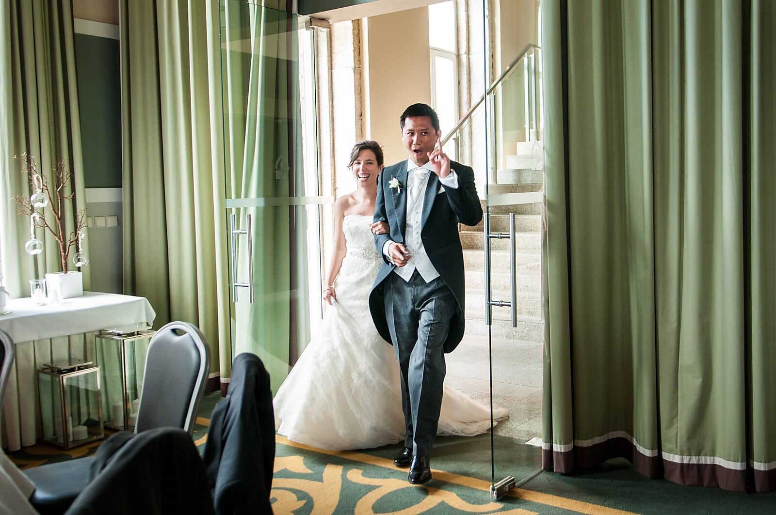 Bride and groom cheer as they enter their wedding reception