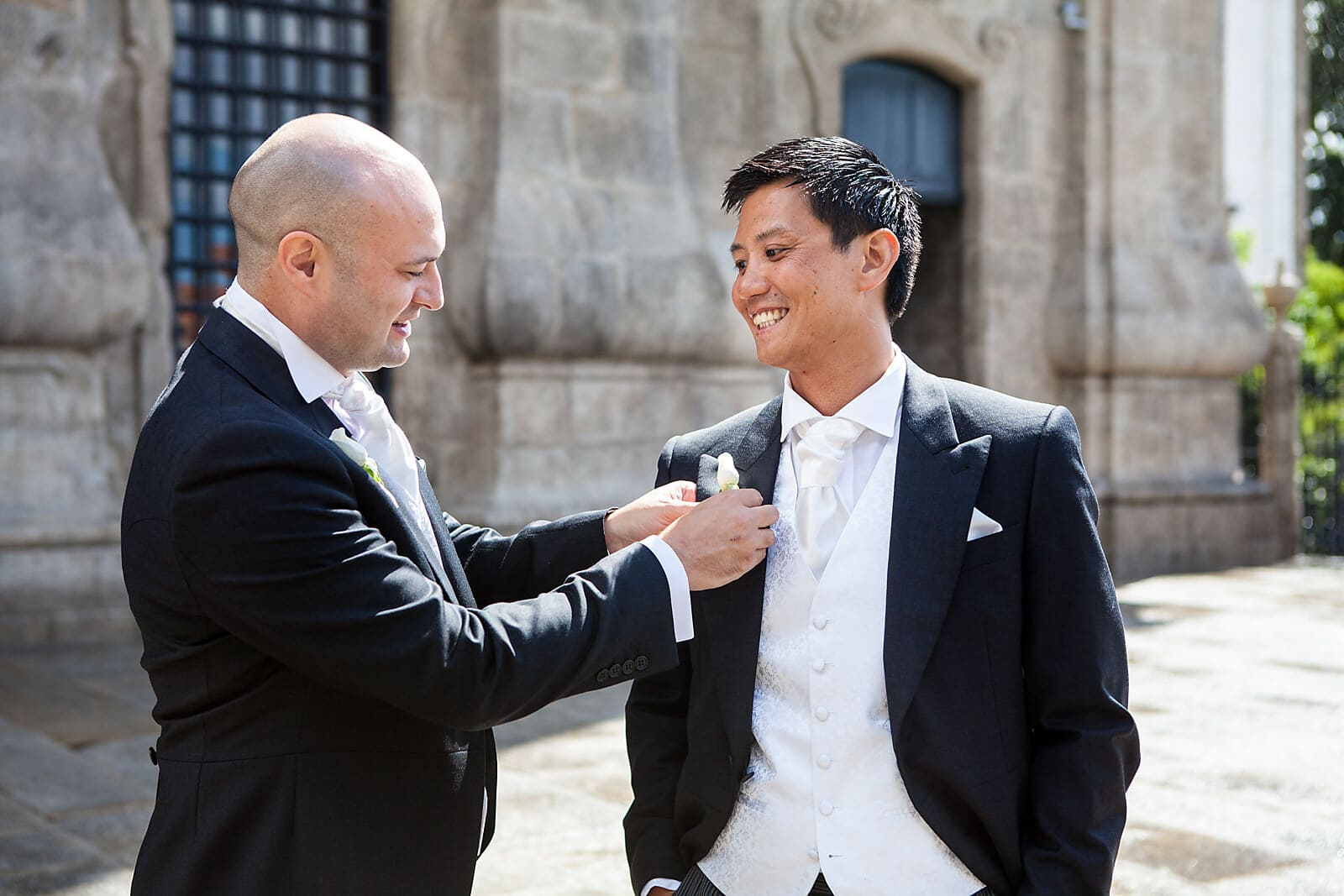 Best man puts on the grooms buttonhole at a Porto church