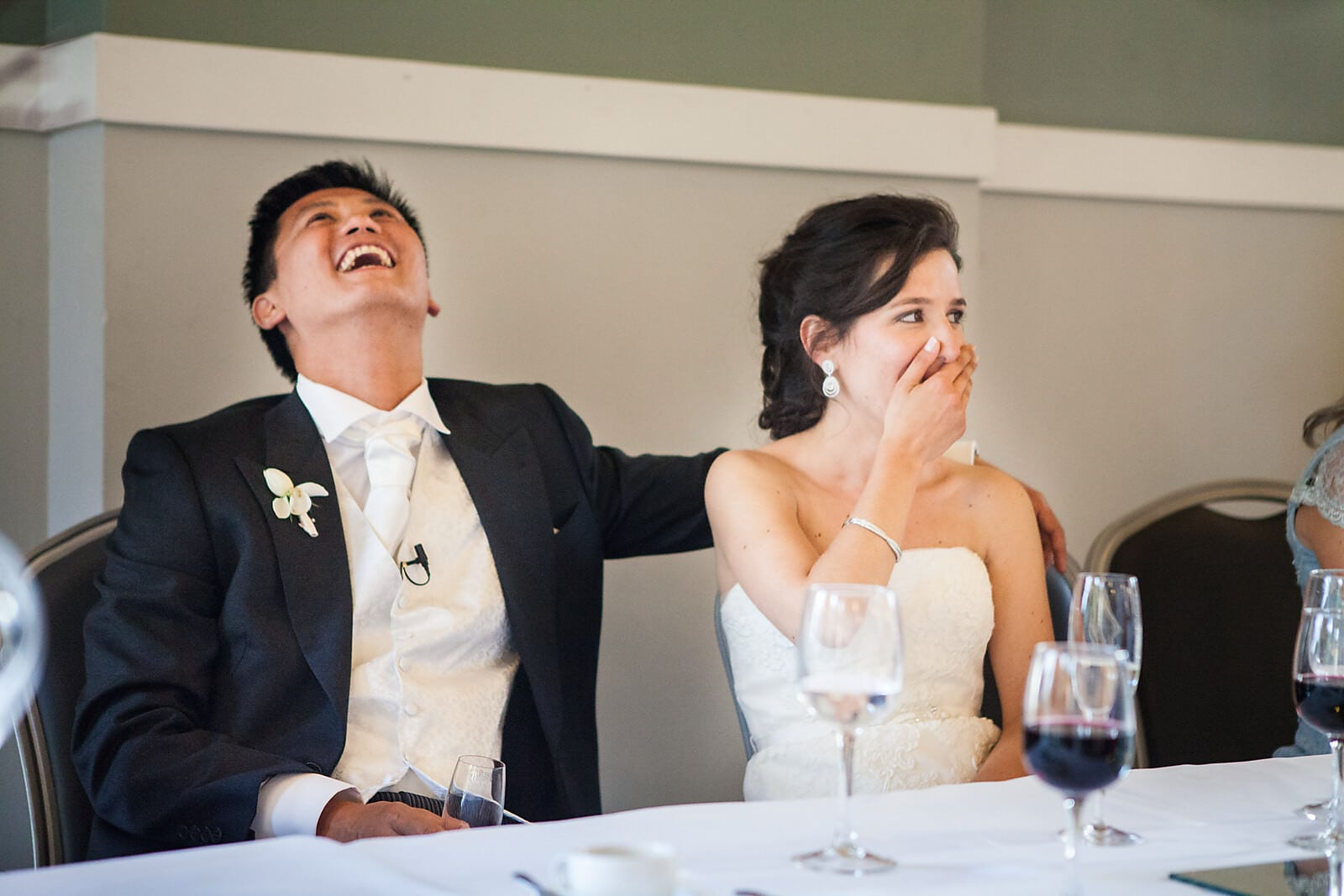 Bride and Groom laugh at the wedding speeches at their Porto Palácio do Freixo Destination Wedding