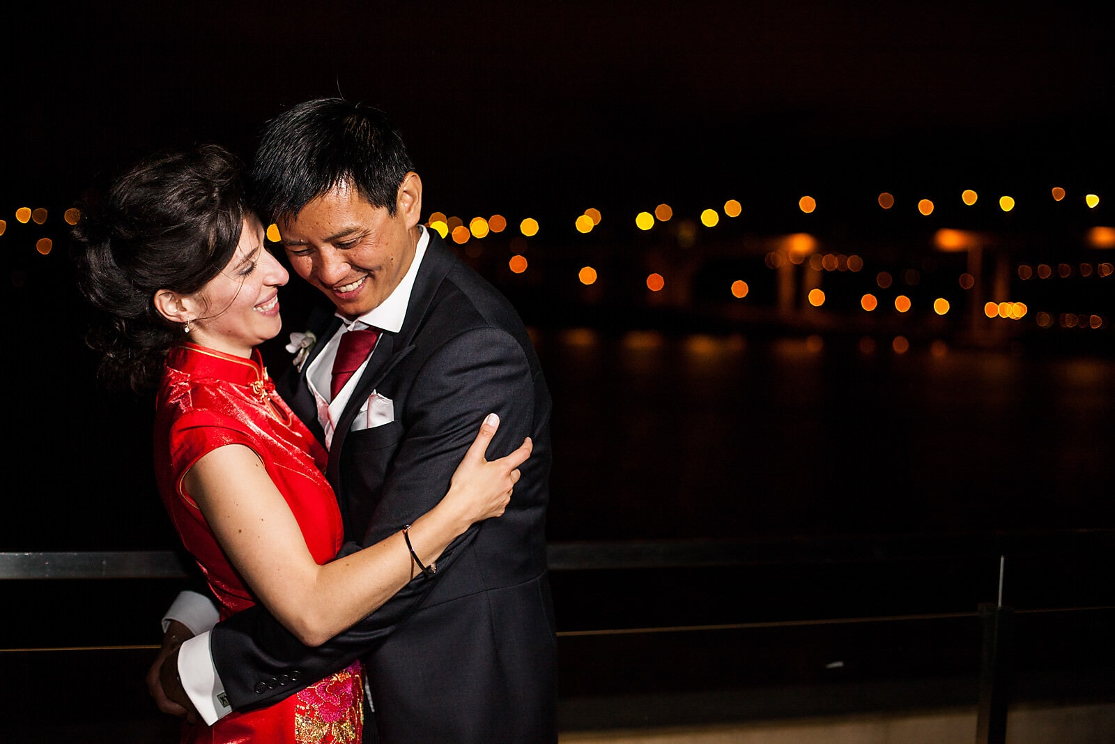 Bride and groom in Chinese wedding outfits hug at night with the Porto bridge in the background