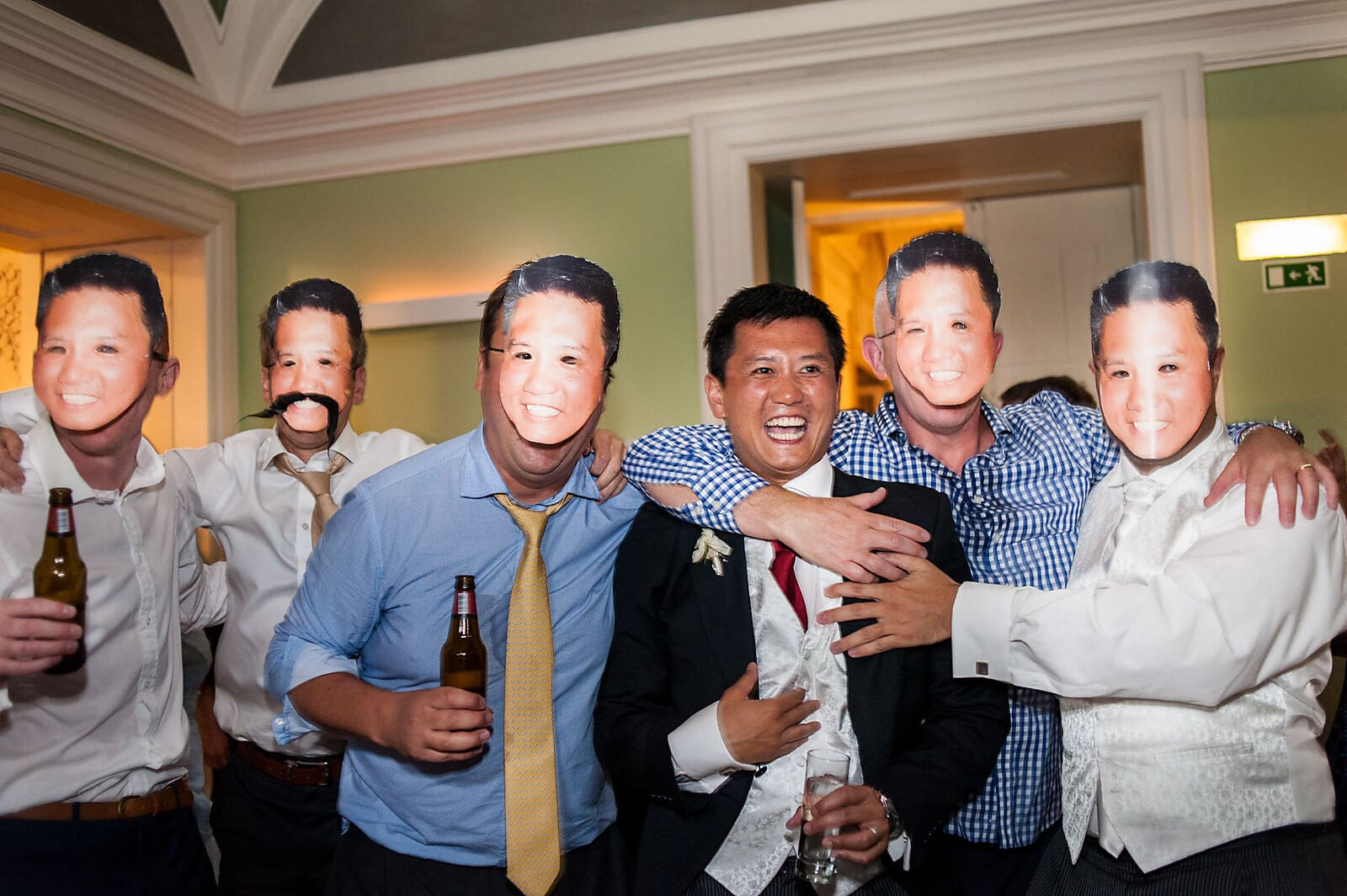Groom dances with groomsmen all wearing his face masks