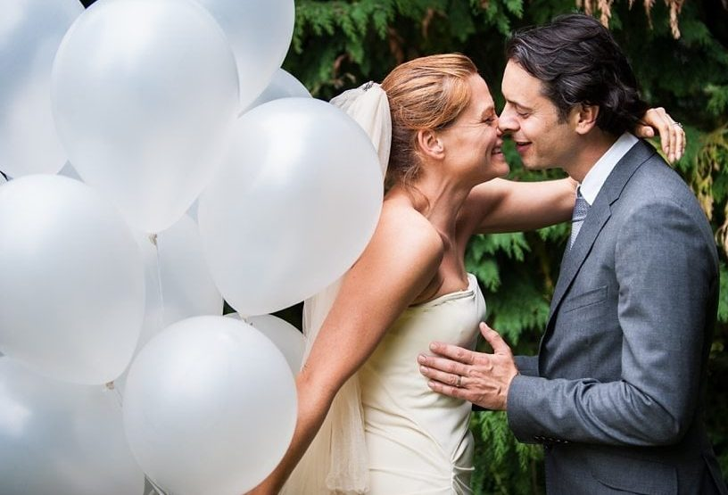 Bride and groom kiss as she holds a bunch of white balloons