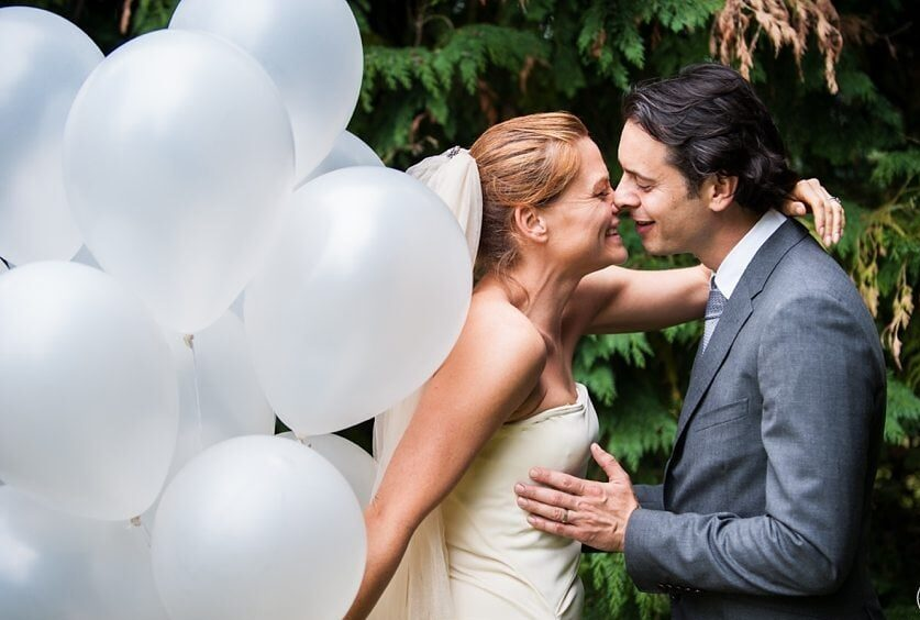 Bride leans in for a kiss and holds white helium balloons