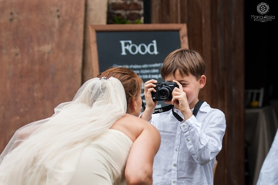 Son taking a photo of the bride at Norfolk wedding