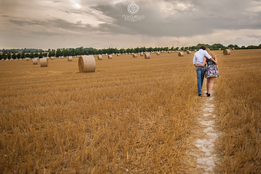 Romantic couple photoshoot, Kent engagement photographer, engaged couple walking through hay field
