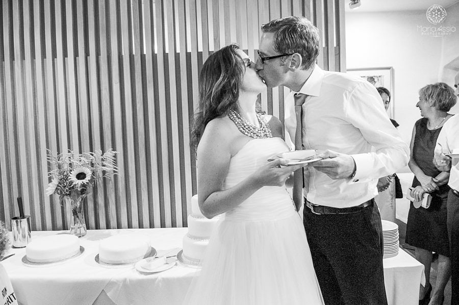 Bride and groom kissing after eating wedding cake
