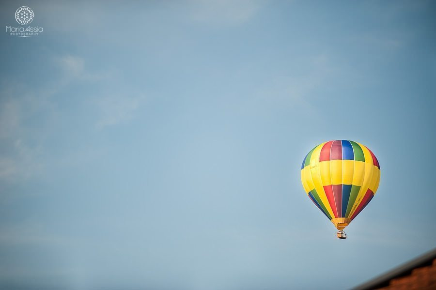 Hot air balloon floating over wedding venue