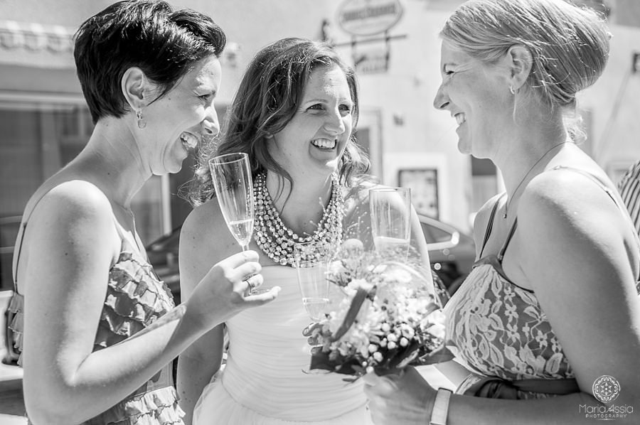 Bride laughing with her friends over champagne