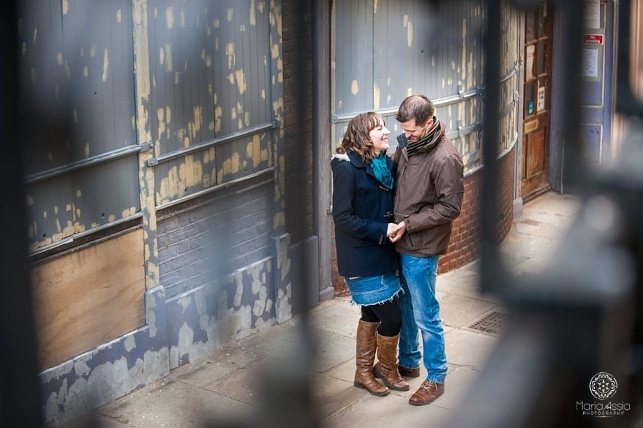 Engaged couple hugging visible through stair railing