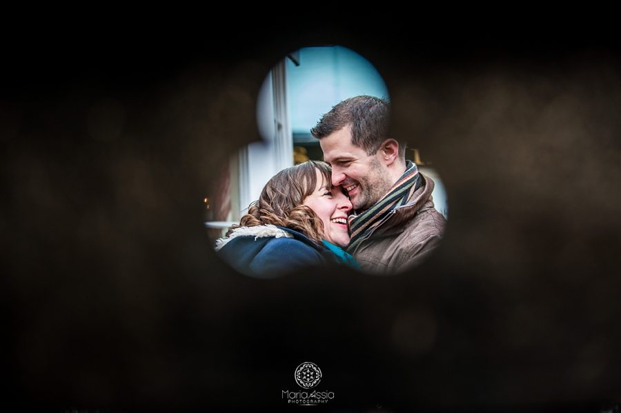 Engaged couple hugging visible through hole in the wall