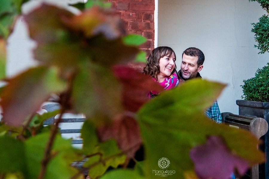Engaged couple laughing between leaves, Christopher Wren Hotel in Windsor