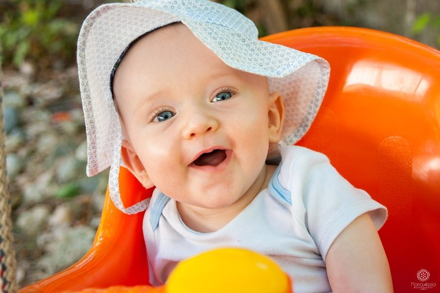 smiling baby with a polka dot sun hat in a swing