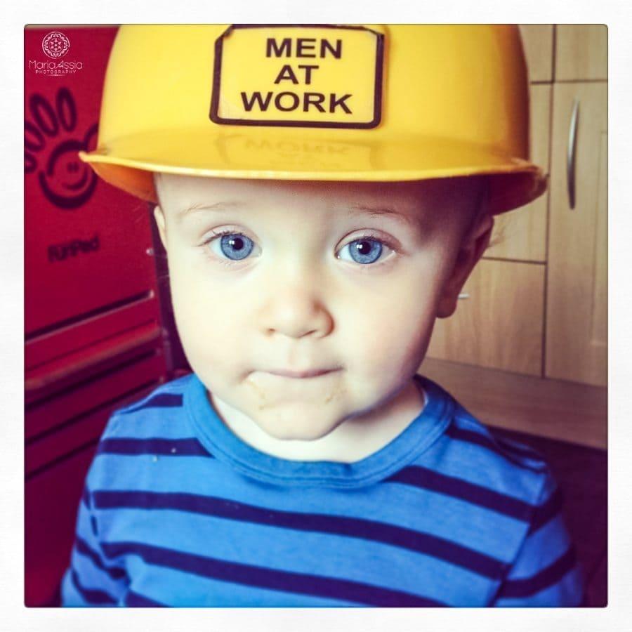 toddler with men at work builder's helmet