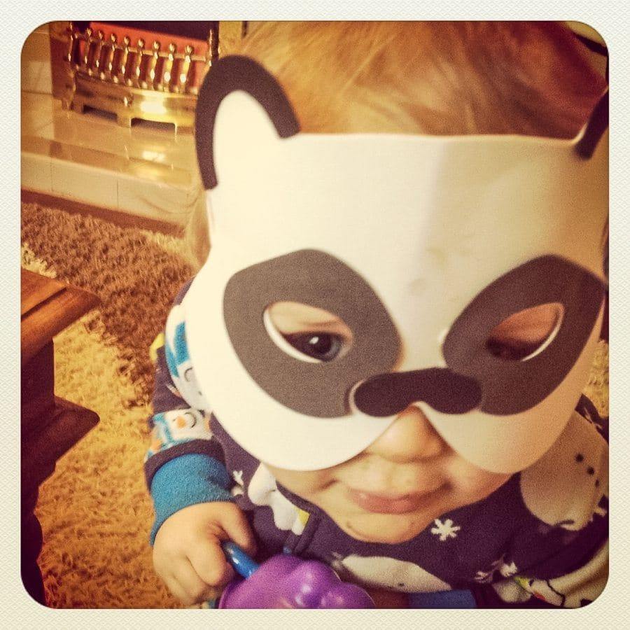 toddler wearing a panda bear mask
