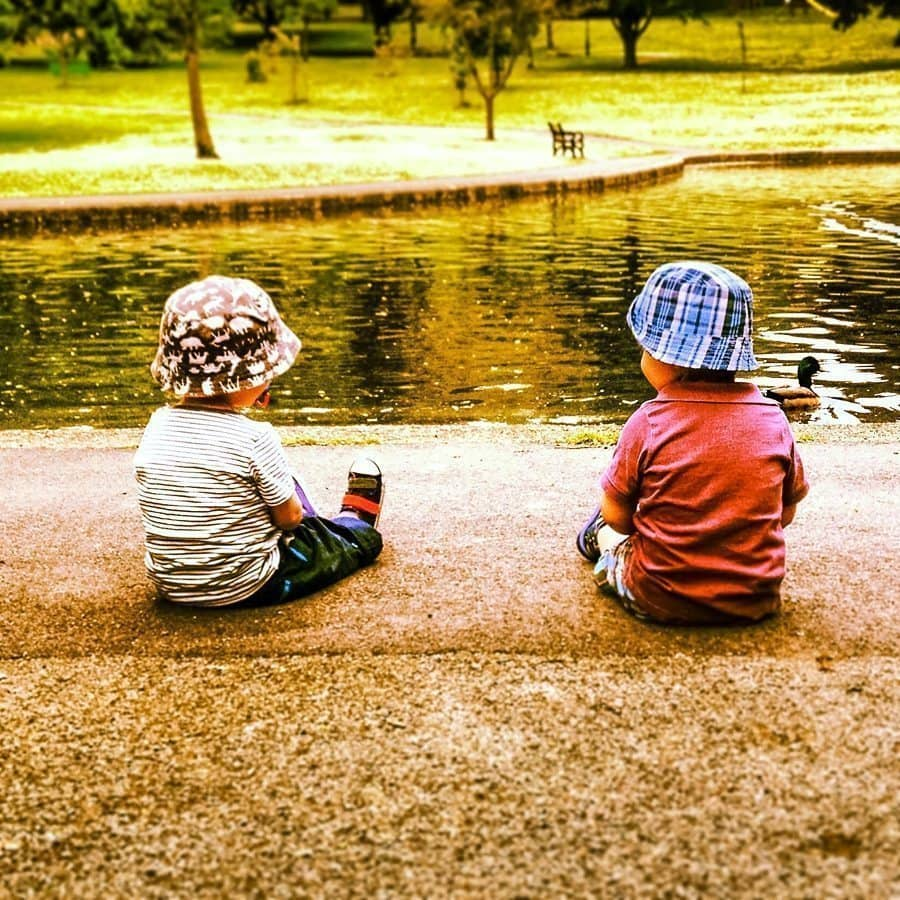 two little boys sitting together a looking over a lake