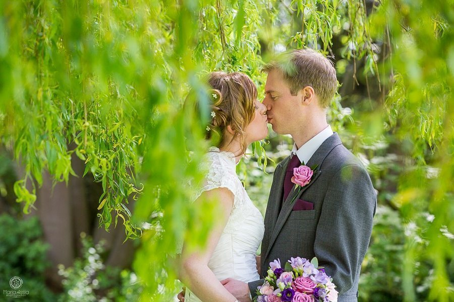 Bride and groom kissing with weeping willow at their Billesley Manor Hotel Fuchsia Spring Wedding