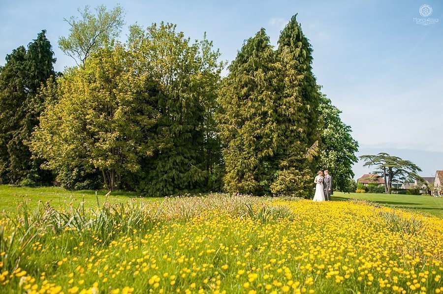 Summer wedding at Billesley Manor Hotel couple shoot in a field of yellow buttercups