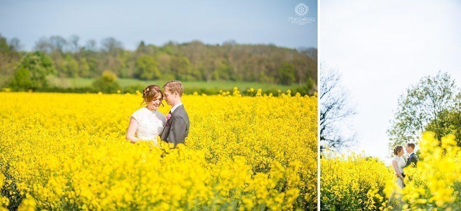 Bride and groom standing in rapeseed field at their Billesley Manor Hotel Fuchsia Spring Wedding