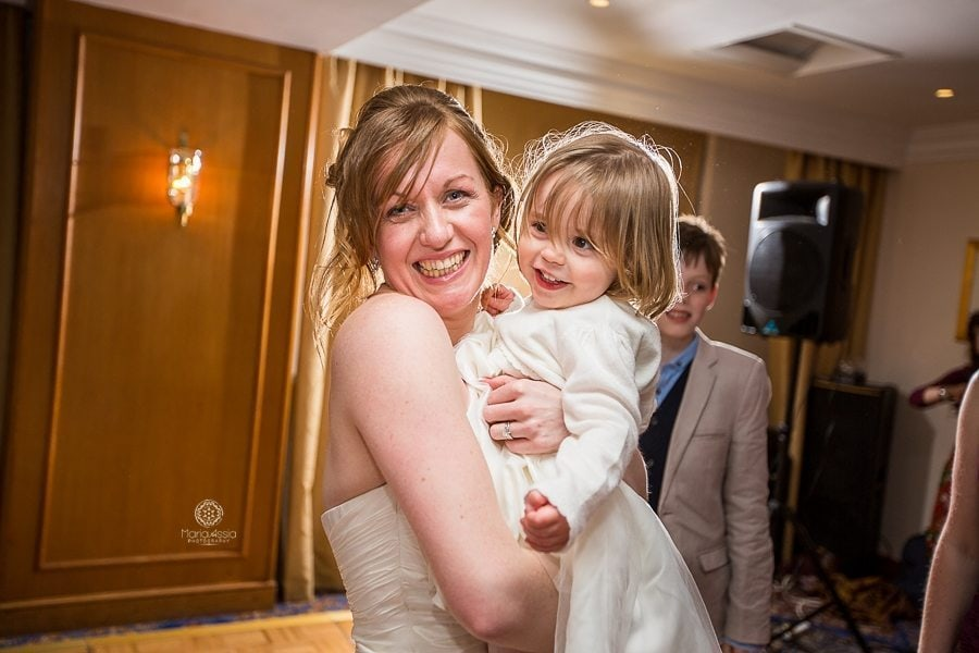 Bride dancing and smiling with her niece at her Billesley Manor Hotel Fuchsia Spring Wedding