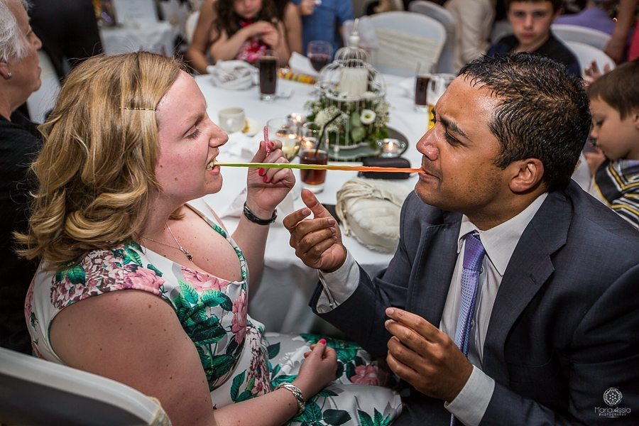 Wedding guests sharing a candy snake at a Billesley Manor Hotel Fuchsia Spring Wedding