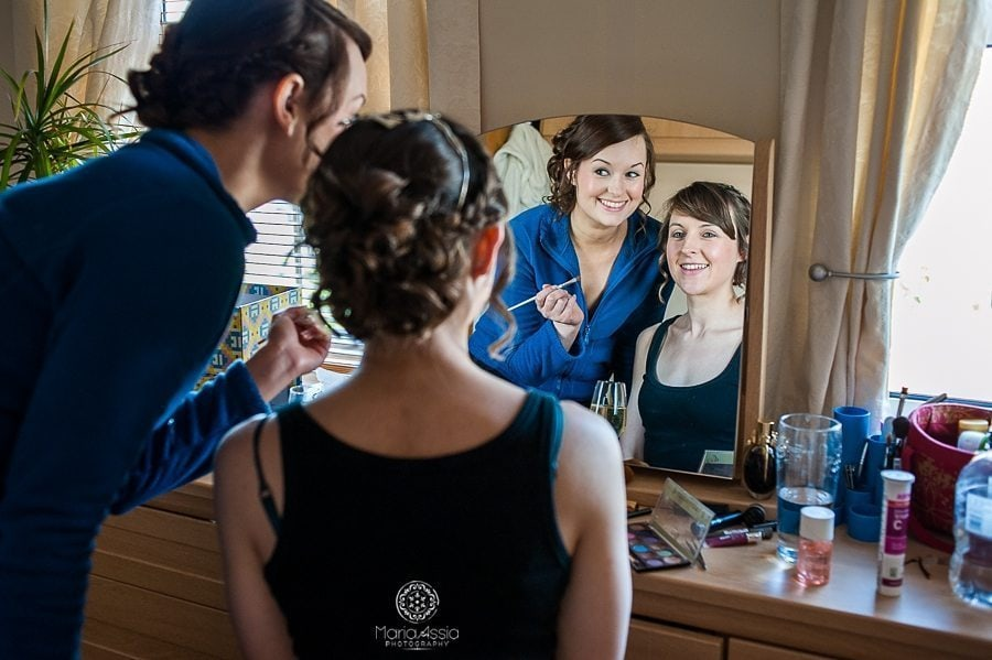 Bride and bridesmaid smiling at each other in the mirror