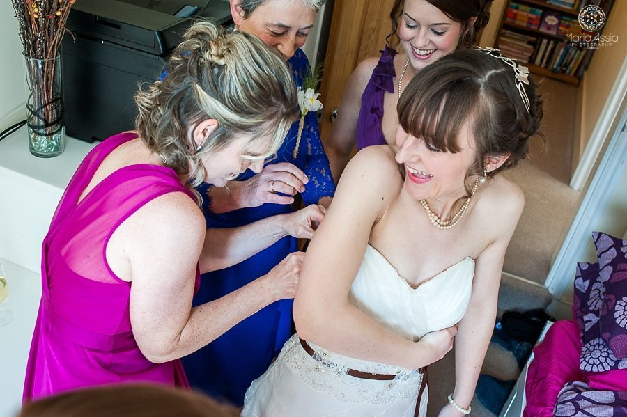 Bridesmaids helping bride into wedding dress for her vintage windsor wedding at the sir christopher wren hotel