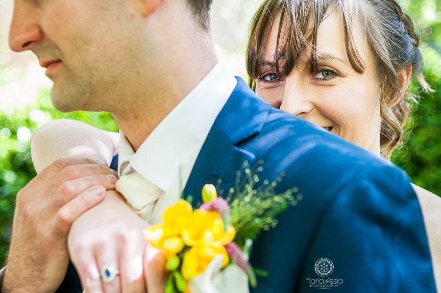 Bride hugging her husband from behind and smiling over his shoulder