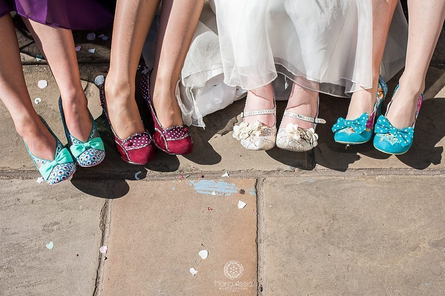Bride sitting down with her bridesmaids at the windsor guildhall steps all wearing irregular choice wedding shoes