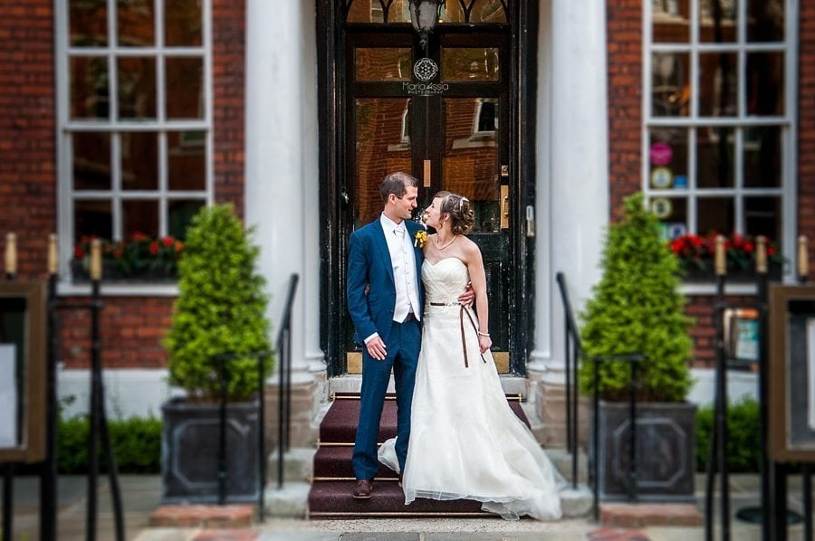 Bride and groom stnading at the entrance of the Sir Christopher Wren Hotel Windsor