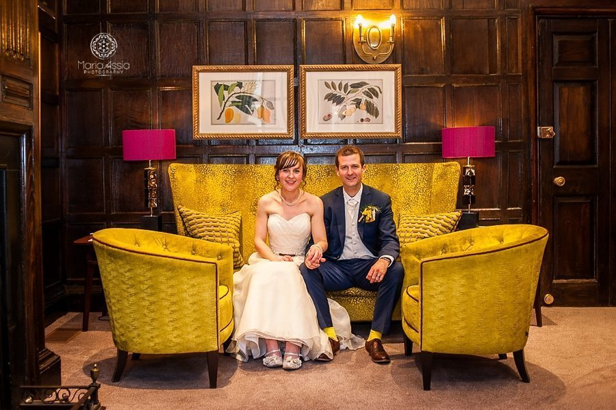 Bride and Groom sitting on a vintage yellow couch at their Windsor Sir Christopher Wren Hotel Wedding